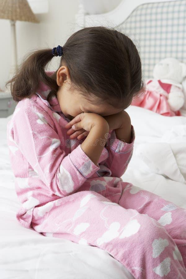 Vermoeid Jong Meisje die Pyjama's dragen die op Bed zitten stock foto's