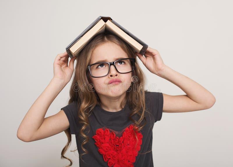 Vermoeid meisje met dak van boek royalty-vrije stock afbeelding
