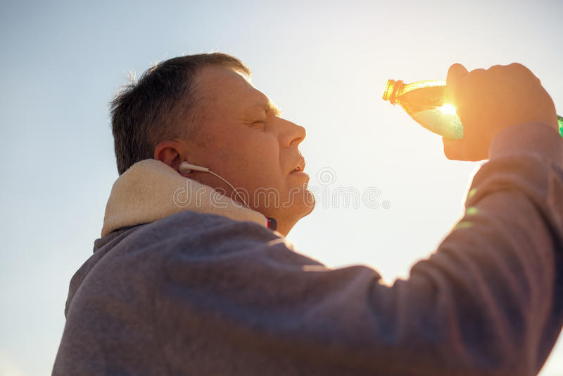 Vermoeid mensen drinkwater van een plastic fles na geschiktheid tim royalty-vrije stock fotografie