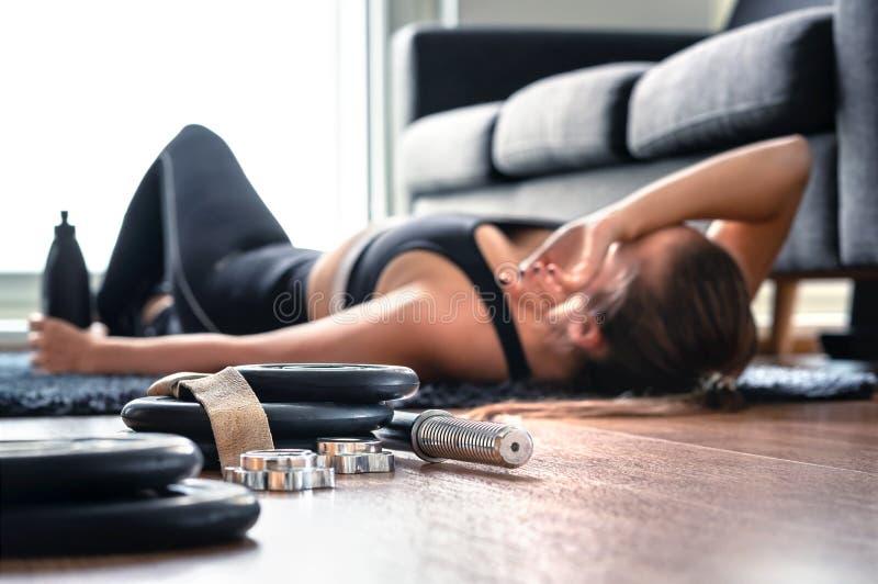 Vermoeid na oefening en training Overtrainingsconcept Uitgeputte vrouw die op en vloer liggen die ademen rusten royalty-vrije stock fotografie
