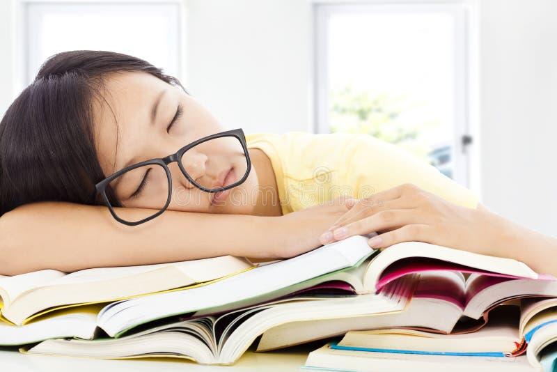 Vermoeid studentenmeisje met glazen die op de boeken slapen stock afbeelding