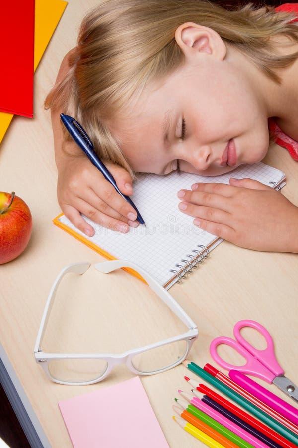 Vermoeid van schoolmeisje in slaap op het bureau royalty-vrije stock foto's