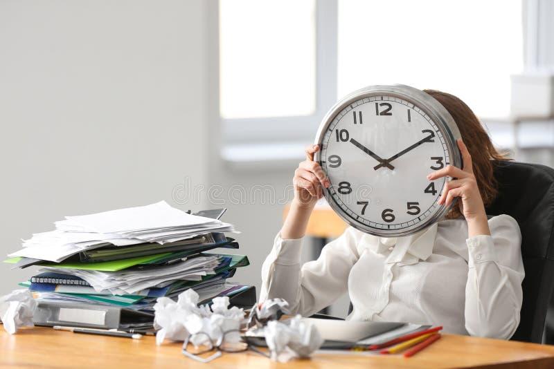 Vermoeid vrouwen verbergend gezicht achter klok bij lijst in bureau Het Concept van het tijdbeheer royalty-vrije stock fotografie