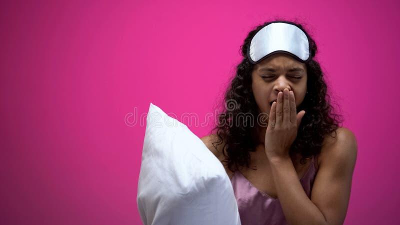 Vermoeide Afrikaans-Amerikaanse vrouw in pyjama's en oogmasker geeuw, die hoofdkussen houden stock foto's
