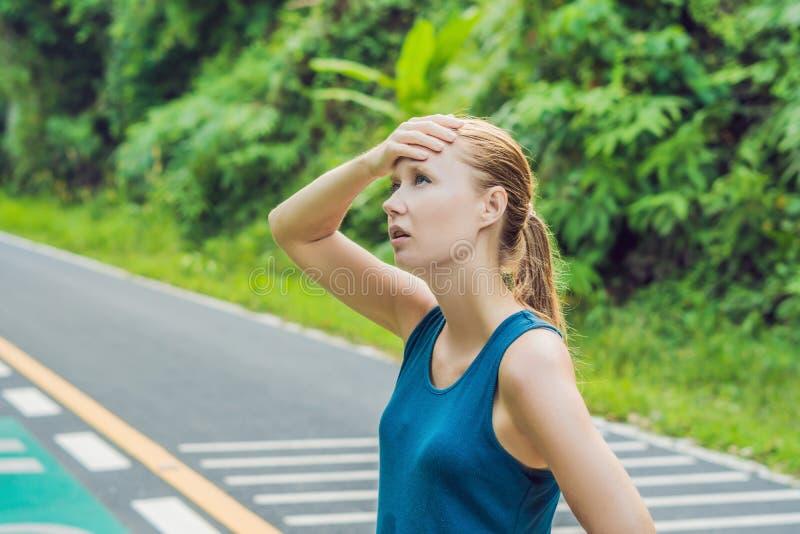 Vermoeide agent die na het lopen hard in plattelandsweg zweten Uitgeputte zwetende vrouw na marathon opleiding op de hete zomer H royalty-vrije stock afbeelding