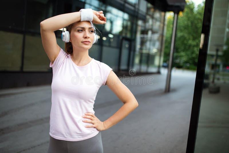 Vermoeide agentvrouw die na openlucht lopen zweten stock fotografie