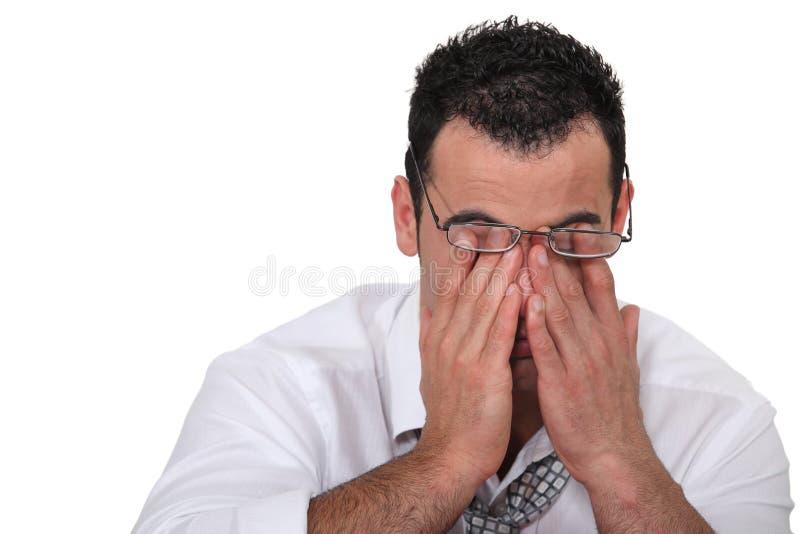 Vermoeide arbeider die zijn ogen wrijft stock afbeelding