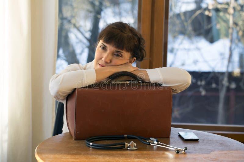Vermoeide arts die op koffer leunen stock afbeelding