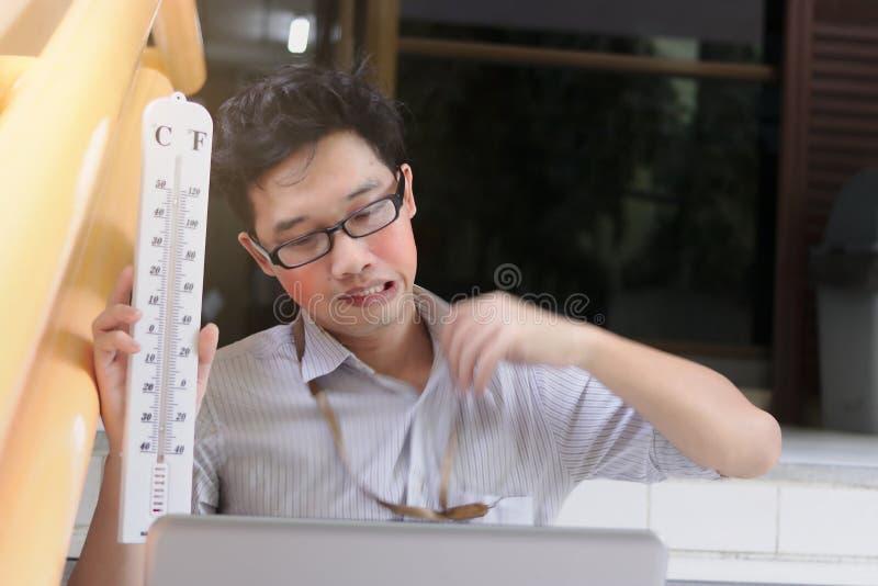 Vermoeide Aziatische bedrijfsmens met thermometer zitting en het zweten na het werk De dagconcept van de de zomerhitte stock fotografie