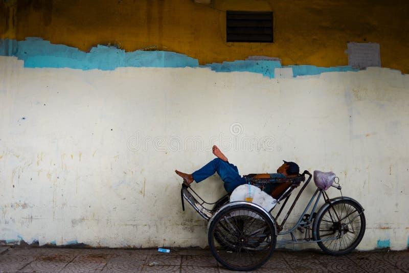 Vermoeide Aziatische cyclobestuurder die een dutje op zijn cyclo met exemplaarruimte nemen voor tekst of op kleurrijke achtergron stock fotografie