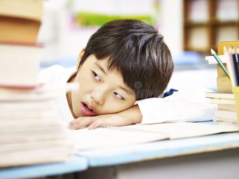 Vermoeide Aziatische elementaire schooljongen royalty-vrije stock afbeelding