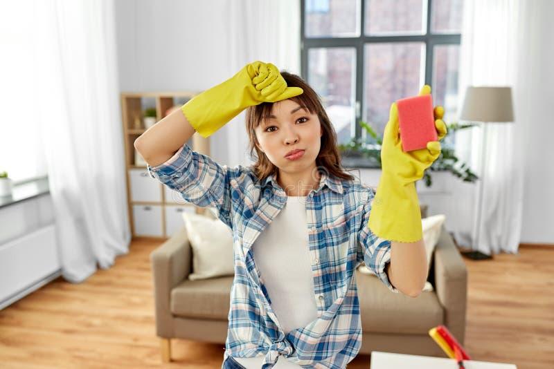 Vermoeide Aziatische vrouw met spons die thuis schoonmaken royalty-vrije stock foto