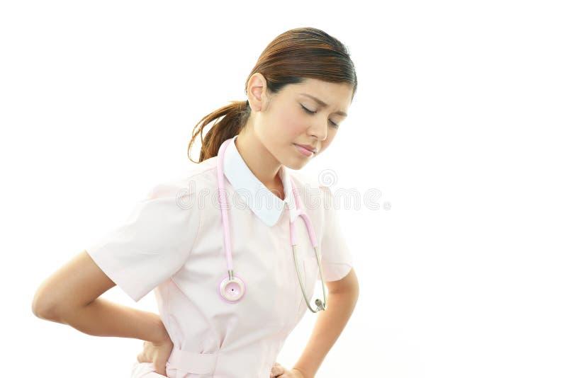 Vermoeide Aziatische vrouwelijke verpleegster royalty-vrije stock afbeeldingen