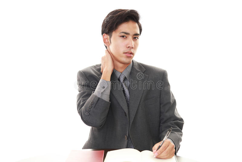 Vermoeide Aziatische zakenman stock afbeeldingen