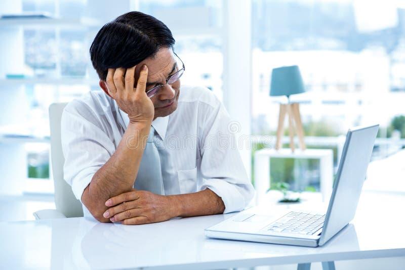 Vermoeide Aziatische zakenman die zijn laptop bekijken royalty-vrije stock afbeeldingen