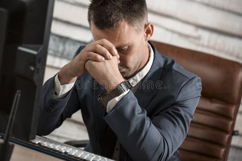 Vermoeide bedrijfsmens die bij werkplaats in bureau zijn hoofd op Ha houden stock foto's