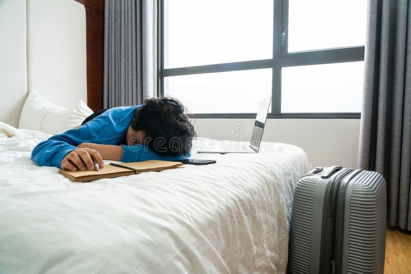 Vermoeide bedrijfsreizigersslaap bij hotelruimte stock foto