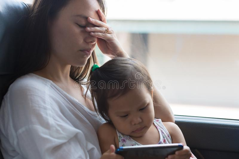 Vermoeide beklemtoonde moeder die een dutje met haar kind nemen stock afbeeldingen