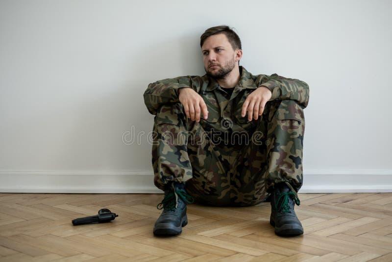 Vermoeide beroepsmilitair in groene eenvormige zitting op de vloer naast een kanon royalty-vrije stock afbeeldingen