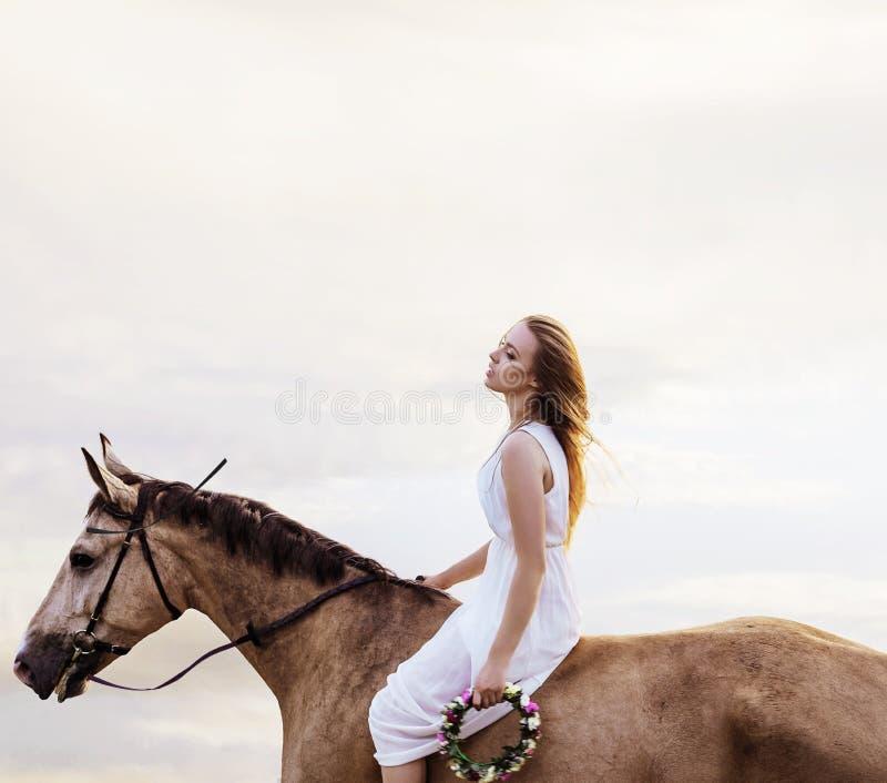 Vermoeide blonde vrouw die door een paard rusten te berijden royalty-vrije stock afbeeldingen