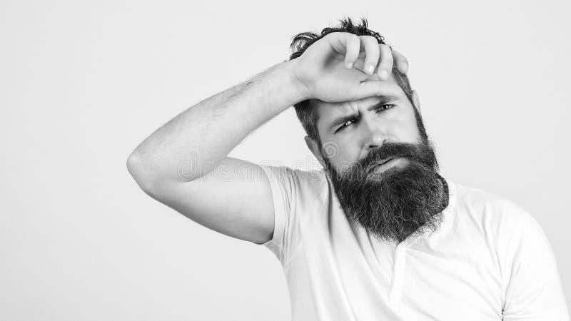 Vermoeide en teleurgestelde jonge gebaarde mens over witte muur De ruimte van het exemplaar Hipsterkerel die moeheid en hoofdpijn stock foto