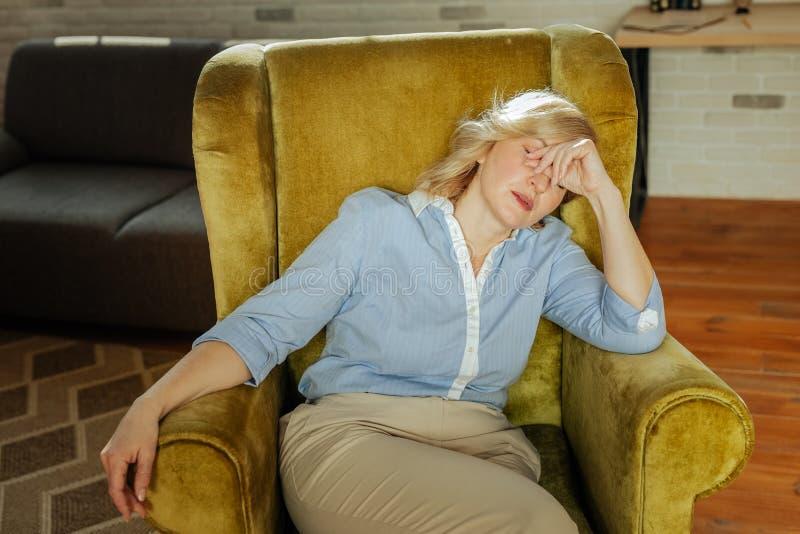Vermoeide gedeprimeerde vrouw die in fluweelleunstoel rusten en haar gezicht sluiten stock foto