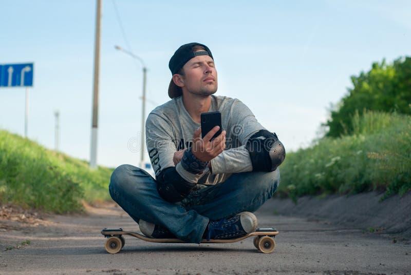 Vermoeide gelukkige jonge schaatser het sluimeren zitting op een skateboard, ademhalings verse lucht Mensen en het concept ontspa royalty-vrije stock afbeelding