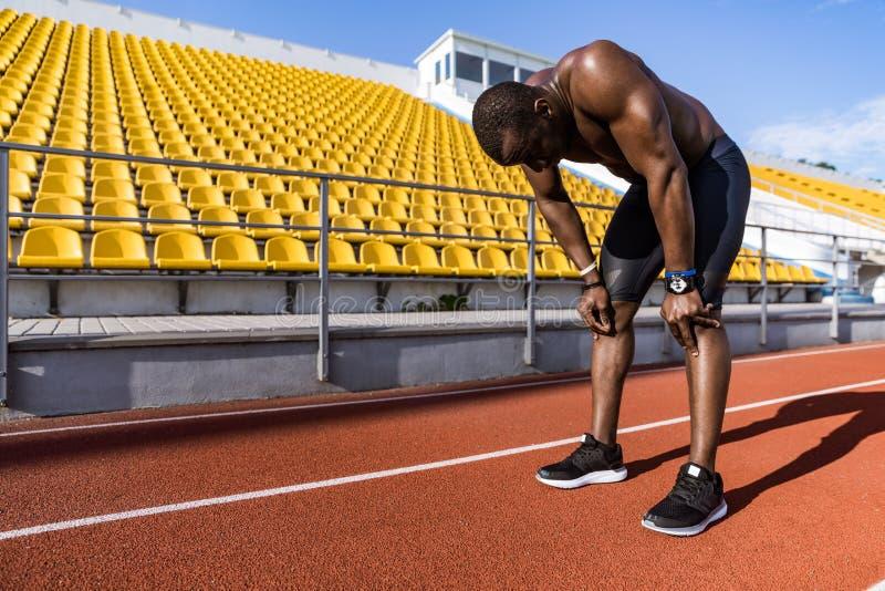 Vermoeide gezonde Afrikaanse sportman die na het lopen rusten stock afbeelding