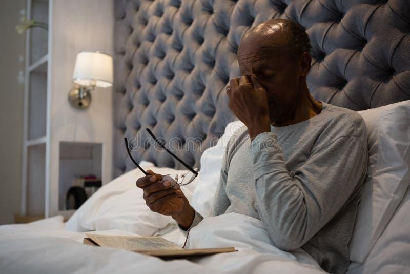 Vermoeide hogere mens die ogen masseren terwijl het houden van oogglazen op bed stock foto's