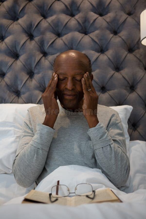 Vermoeide hogere mens die ogen masseren terwijl het zitten op bed stock fotografie