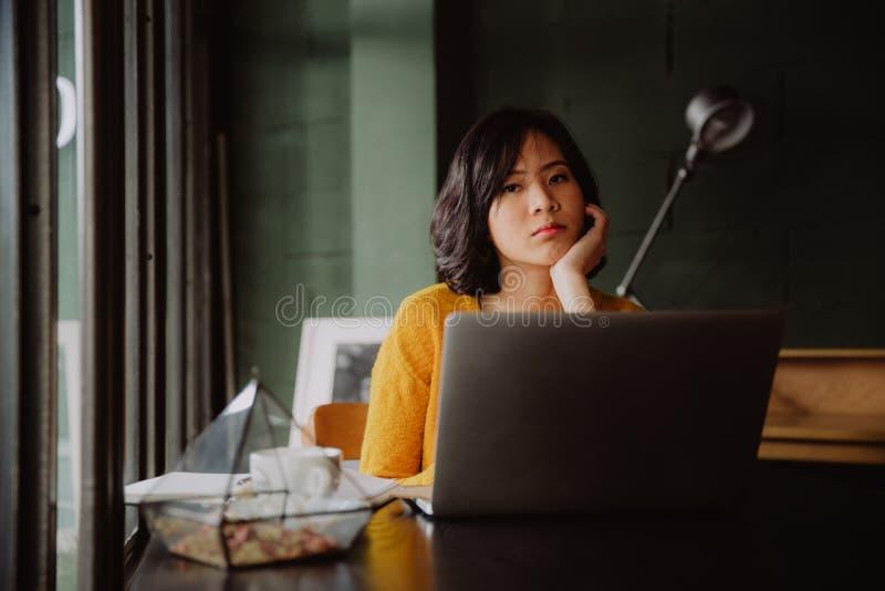 Vermoeide jonge Aziatische vrouw in haar bureau royalty-vrije stock afbeeldingen