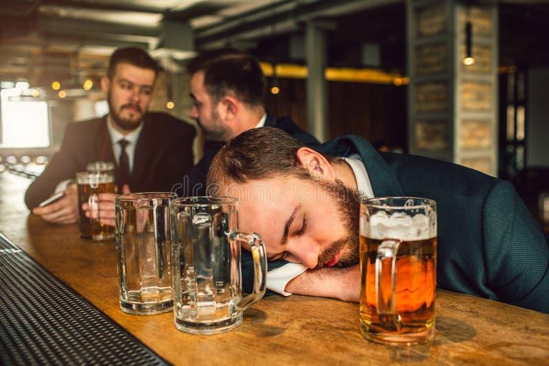 Vermoeide jonge mens in kostuumslaap op barteller hij is gedronken er zijn twee lege mokken en één hoogtepunt met bier Andere twe stock foto