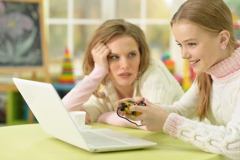 Vermoeide jonge moeder die dochter bekijken die het spelen videospelletjes royalty-vrije stock afbeeldingen