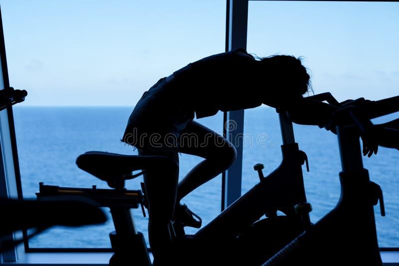 Vermoeide jonge vrouw die bij het spinnen van fiets situeren royalty-vrije stock foto