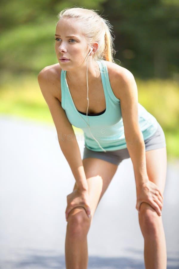 Vermoeide jonge vrouw die haar adem na lang vangen - gelopen stock afbeeldingen