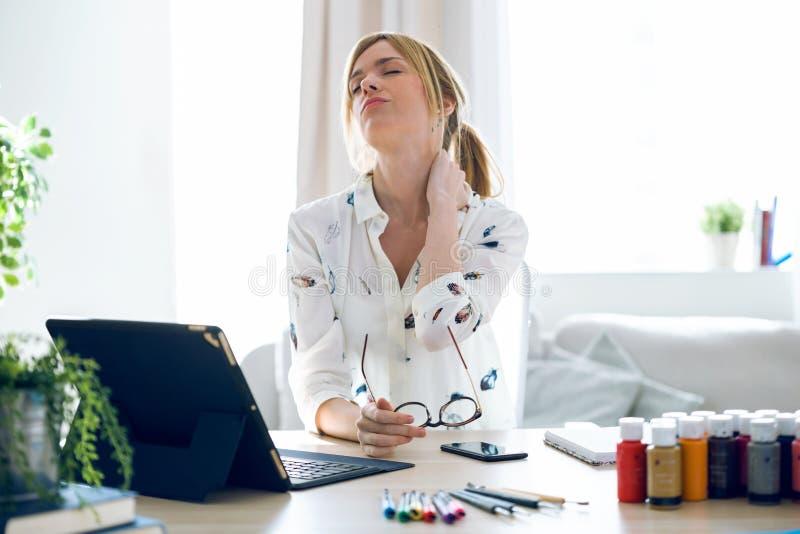 Vermoeide jonge vrouw die met halspijn met haar digitale tablet op het kantoor werken stock foto's