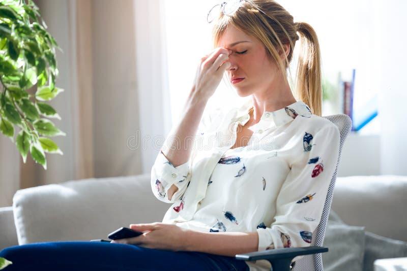 Vermoeide jonge vrouw met hoofdpijn die haar mobiele telefoon houden op het kantoor royalty-vrije stock fotografie