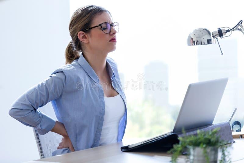 Vermoeide jonge vrouw met rugpijn die haar laptop thuis met behulp van stock afbeeldingen