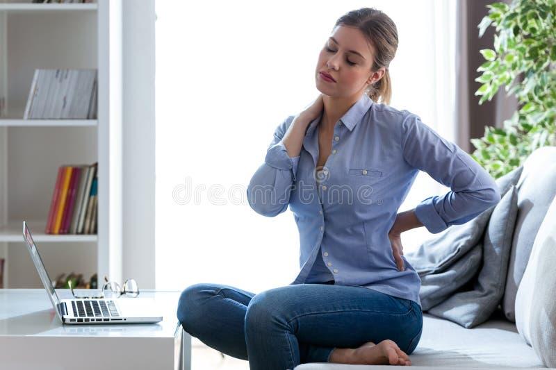Vermoeide jonge vrouw met schouder en rugpijnzitting op de laag thuis stock foto