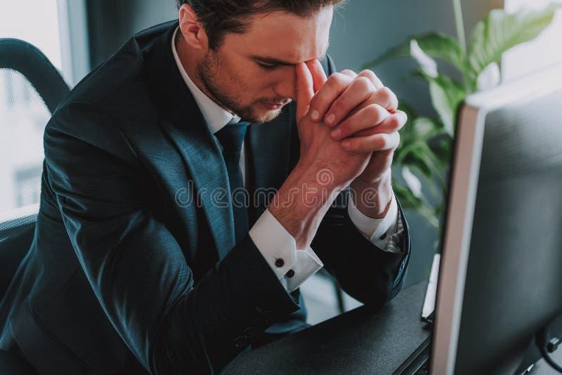 Vermoeide jonge zakenman wat betreft zijn gezicht en sluitende ogen royalty-vrije stock afbeelding