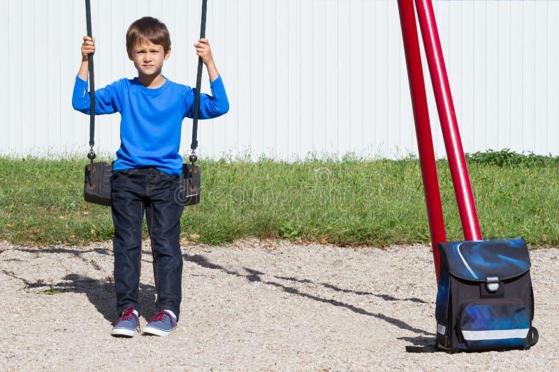 Vermoeide jongen na schoolzitting op de schommeling stock fotografie