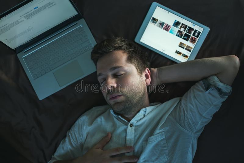 Vermoeide Kaukasische jonge mens in wit overhemd die en één hand boven hoofd slapen houden, die op bed dichtbij laptop liggen royalty-vrije stock fotografie