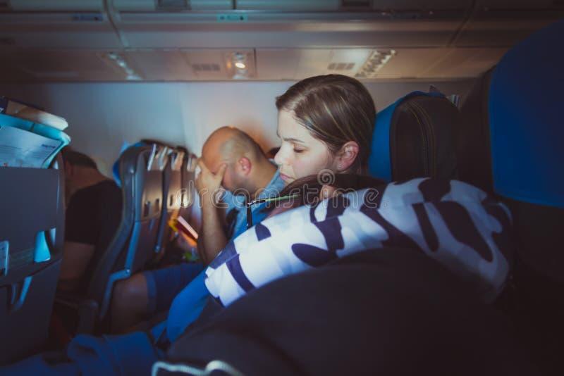 Vermoeide Kaukasische mannen en vrouwen die op zetels slapen terwijl het reizen stock fotografie