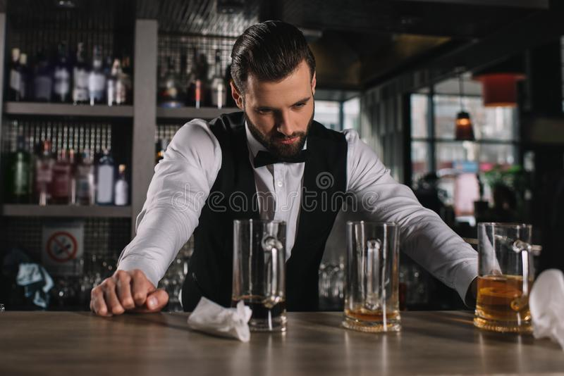 vermoeide knappe barman die op barteller leunen en vuile glazen bekijken royalty-vrije stock foto