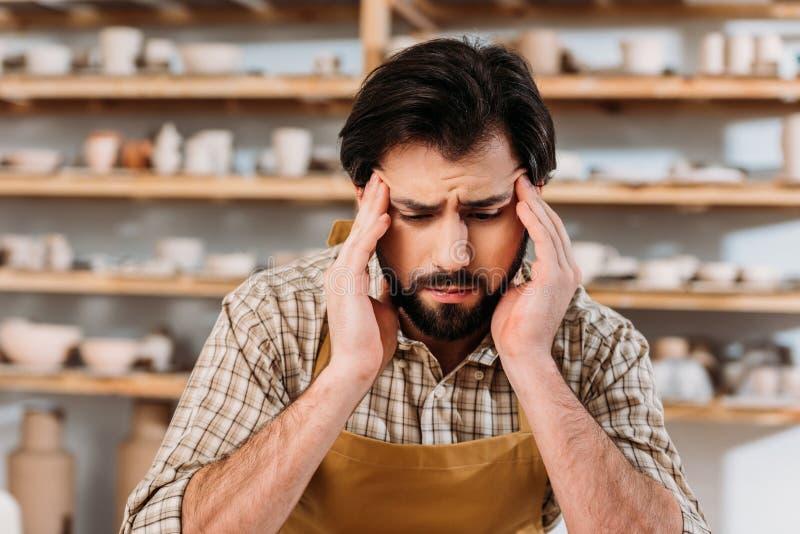 vermoeide mannelijke pottenbakker die hoofdpijn hebben terwijl het zitten royalty-vrije stock afbeelding
