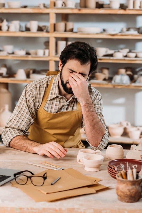 vermoeide mannelijke pottenbakker in schortzitting bij lijst met keramiek stock afbeeldingen