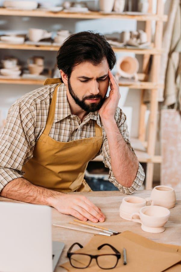vermoeide mannelijke pottenbakker in schortzitting stock afbeelding
