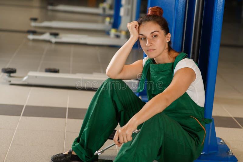 Vermoeide meisjes mechanische rust dichtbij een autolift stock fotografie