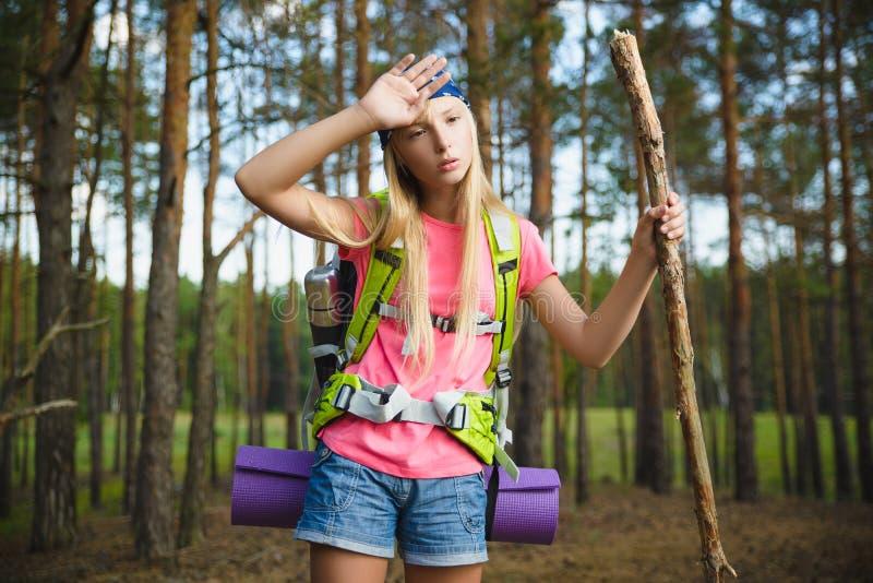 Vermoeide Meisjesreiziger met rugzak in bosavontuur, reis, toerismeconcept stock foto