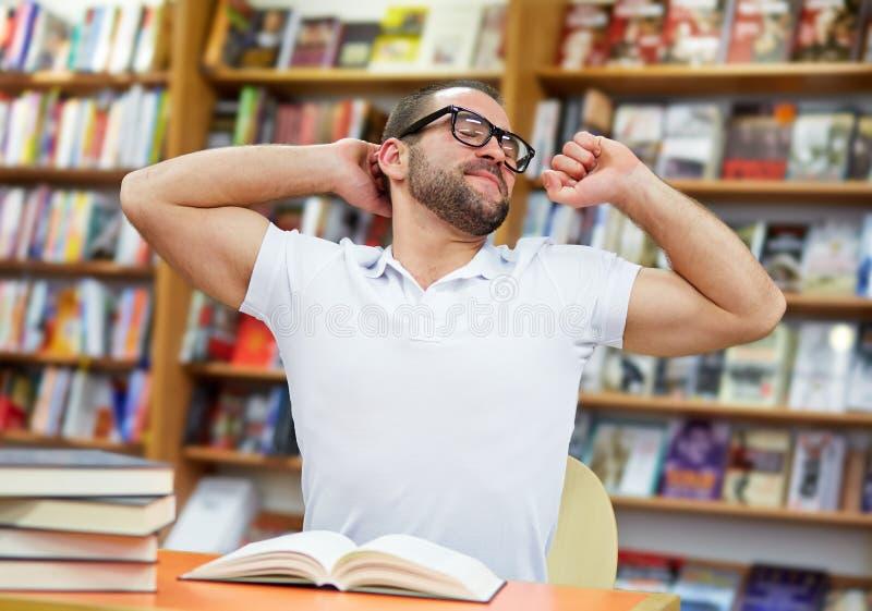 Vermoeide mens in de bibliotheek stock afbeeldingen